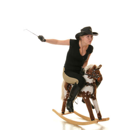 adult toys: Young beautiful cowgirl (jockey) race on hobbyhorse with face expression isolated on white background (race concept). Stock Photo