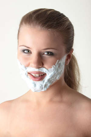 Happy pretty young woman with white beard made of shaving foam over white background photo