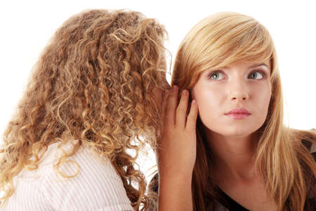 hearsay: Two happy young girlfriends talking isolated over white Stock Photo
