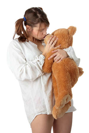 Young beautiful teen woman in long shirt with her teddy bear, isolated on white background photo