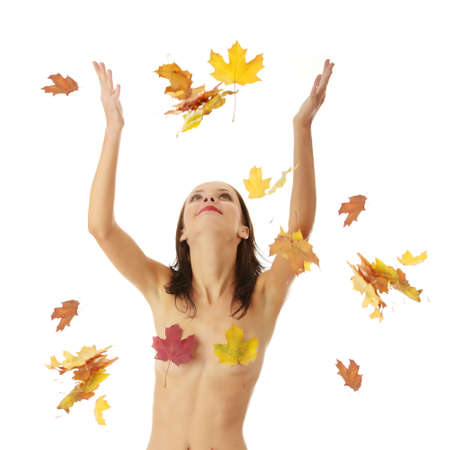 Young nude caucasian woman playing with autumn colorful leaves. Isolated on white photo
