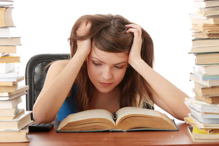 struggling: Teenage girl studying at the desk being tired, isolated on white  Stock Photo