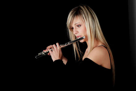 the transverse: Portrait of a woman playing transverse flute, isolated on black Stock Photo