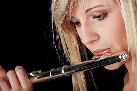 Portrait of a woman playing transverse flute, isolated on black Stock Photo