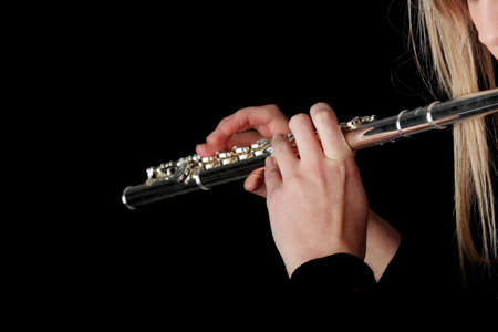rehearse: Portrait of a woman playing transverse flute, isolated on black Stock Photo