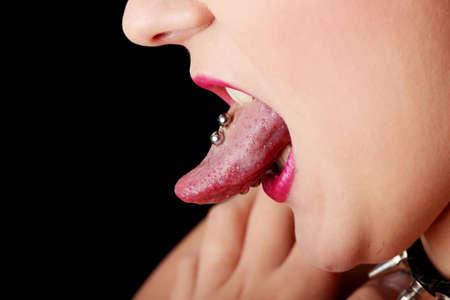 durchbohrt: Frau, die ihre Zunge kleben, zeigen isoliert auf schwarz piercing,
