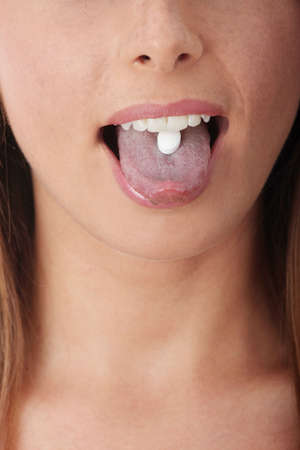 ingest: Extreme close-up image of a young woman taking a pill.  Stock Photo