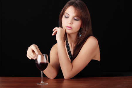 Young woman with glass of red wine, isolated on black background photo