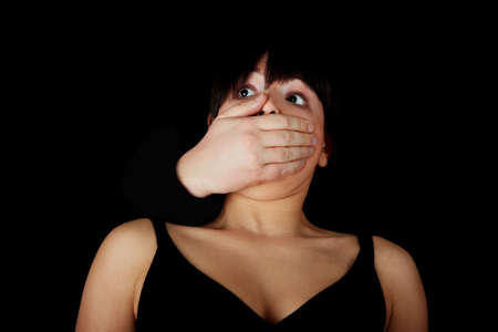 silenced: Young woman is being silenced by man, isolated on black