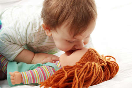 Baby girl kissing her doll isolated on white background photo