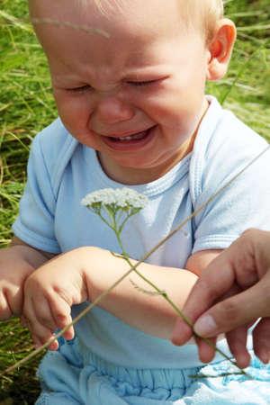 Crying baby boy outdoors at sunny summer day   photo