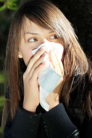 Teen Girl blowing her nose outdoors in late autumn. Stock Photo - 6321335