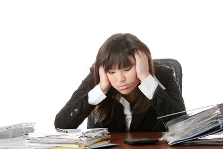filling out: Exhausted female filling out tax forms while sitting at her desk. Isolated Stock Photo