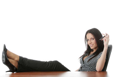 Young businesswoman relaxing at the desk, legs up, over white background photo