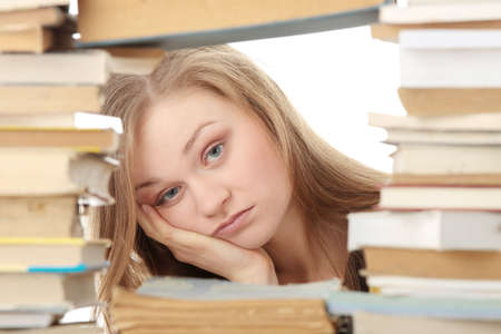 Young woman sitting behind books - tired Stock Photo