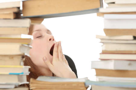 yawing: Young woman sitting behind books - tired Stock Photo