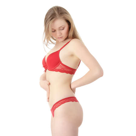Beautiful caucasian woman in red lingerie with hand on her belly isolated on white background photo