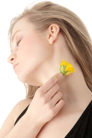 Sensual portrait of young sexy blond woman in black dress using yellow rose like pefume, isolated on white photo