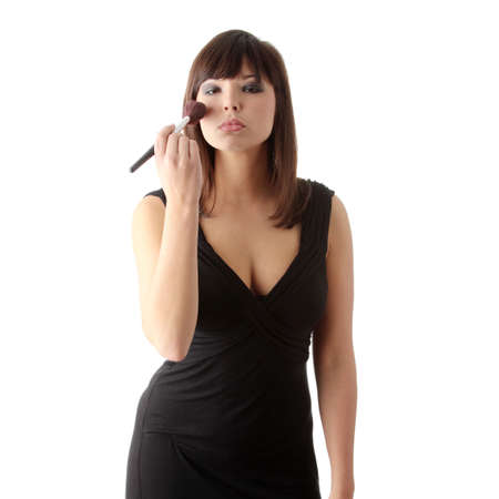 The beautiful young woman in elegant black dress does a make-up, isolated on a white background  photo