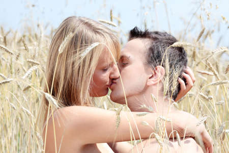A beautiful couple sitting an kissing in wheat field photo