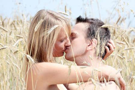 s embrasser: Un beau couple assis un baiser dans le champ de bl�