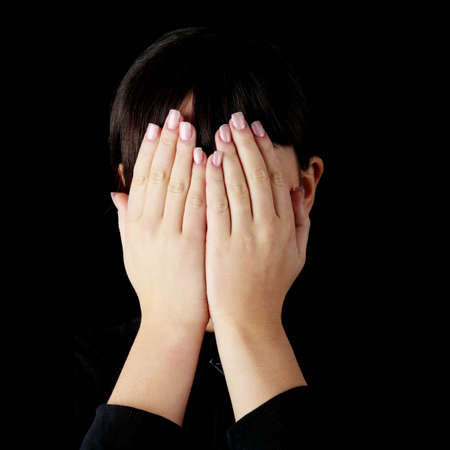 covering: Young woman covering her eyes isolated on black background