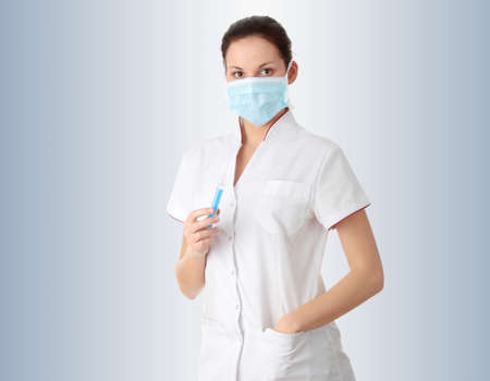Young nurse in mask with syringe,  over gray background photo