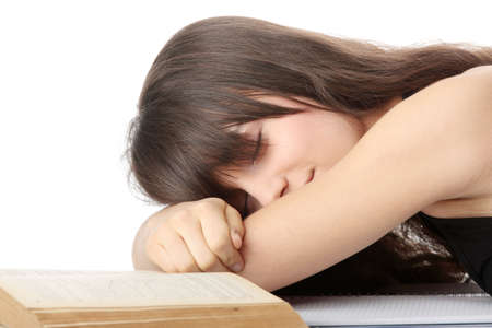 Sleeping while learning - tired teen woman sleeping on desk, over white background photo
