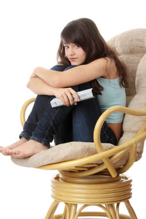 teen legs: Teen woman watching TV with remote control while sitting on armchair view from TV  Stock Photo