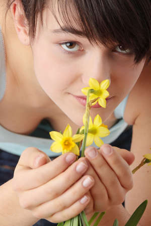 Teen girl smelling yellow spring flowers  photo