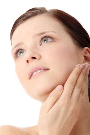 humidify: Woman applying moisturizer cream on face. Close-up fresh woman face.