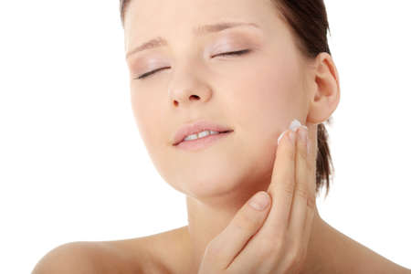 Woman applying moisturizer cream on face. Close-up fresh woman face.  Stock Photo - 6599330