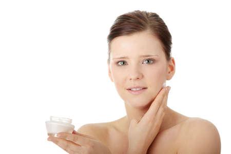 Woman applying moisturizer cream on face. Close-up fresh woman face. Stock Photo - 6599312