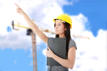 Engineer woman in yellow helmet pointing on something photo