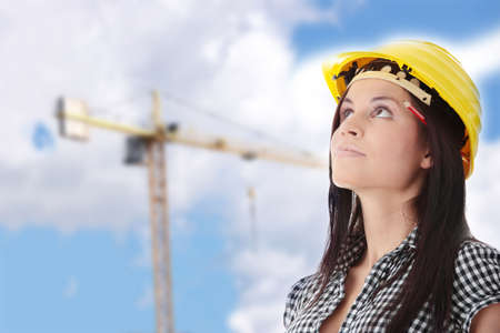 female architect: Engineer woman in yellow helmet looking up i