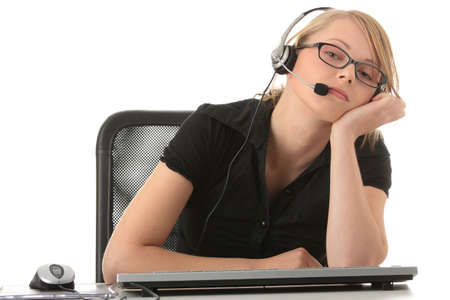callcenter: Young beautiful girl in headset,sitting at the desk bored, isolated on white background  (call center or e learning concept) .