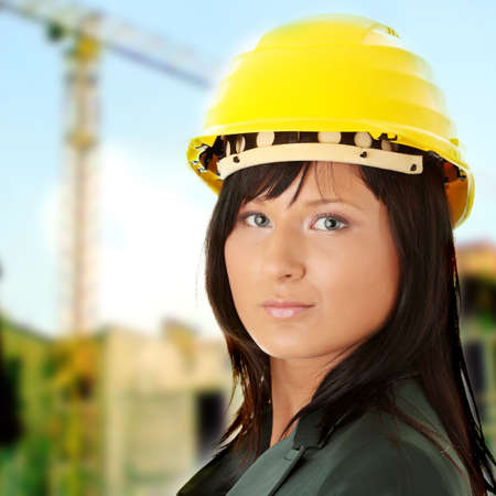 Young female architect or builder wearing a yellow hart hat on a construction site photo