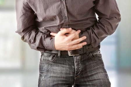 dolor de estomago: Un hombre que se sostiene su est�mago porque tiene diarrea