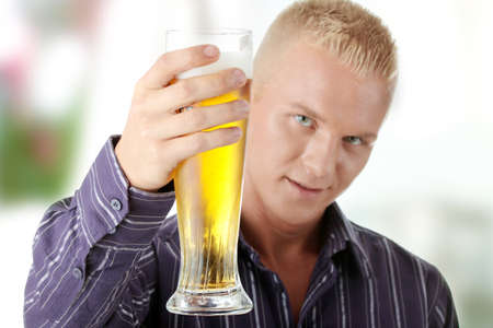 Happy young man holding a glass of beer photo