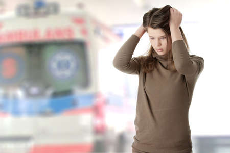 Young beautiful woman with depression - ambulance in background photo