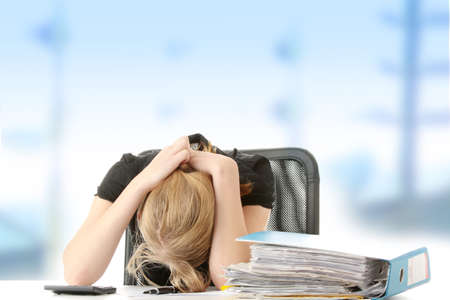account executives: Tired female executive filling out tax forms while sitting at her desk. Stock Photo