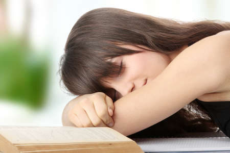 pregui�oso: Sleeping while learning - tired teen woman sleeping on desk Banco de Imagens