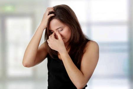 hoofdpijn: Vrouw met hoofd pijn die haar hand op het hoofd