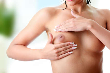 Young Caucasian adult woman examining her breast for lumps or signs of breast cancer isolated on white background Stock Photo