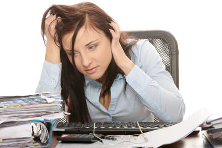 Exhausted female filling out tax forms while sitting at her desk. Isolated photo