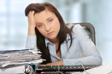 account executives: Exhausted female filling out tax forms while sitting at her desk.  Stock Photo
