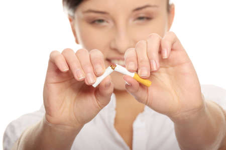 non toxic: Young woman breaking cigarette over white background Stock Photo