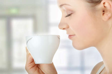 Young attractive blond woman drinking coffee in office - blured background photo