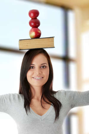 Beautiful student woman with orthodontic appliance have book and three apples on her head - learning concept photo