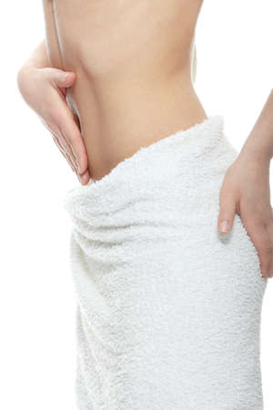 Beautiful woman s flat belly and body covered with towel  Spa concept  photo